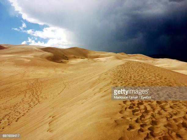 view of desert against cloudy sky - maddison stock photos and pictures