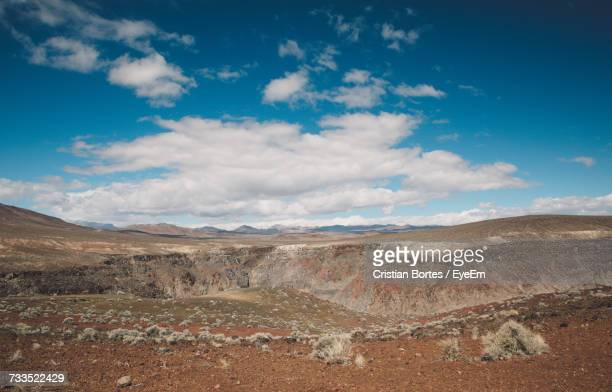 view of desert against cloudy sky - bortes foto e immagini stock
