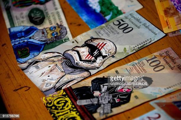 View of devalued Bolivar bills painted by Venezuelan illustrator Jose Leon at his workshop in San Cristobal Venezuela on February 2 2018 Using...