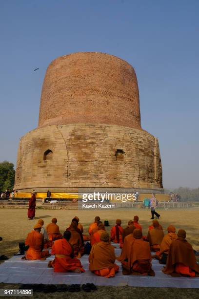 A view of Dhamek Stupa with visiting Budhist pilgrims sat on the ground facing the stupa on January 30 2018 in Sarnath India Dhamek Stupa which is...