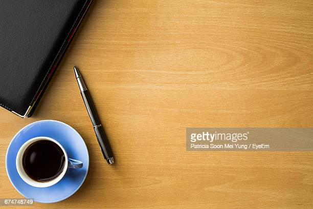 View Of Diary By Pen And Black Coffee On Wooden Table