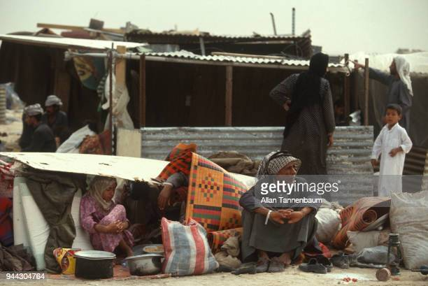 View of displaced men women and children as surrounded by their belongings they sit under and beside a makeshift shelter at a refugee camp during the...