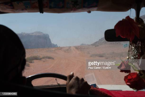 view of driver's hand on steering wheel, driving through desert - jordanian workforce stock pictures, royalty-free photos & images