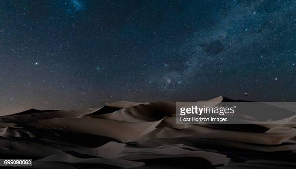 View of dunes under starry night sky, Namib Desert, Namibia