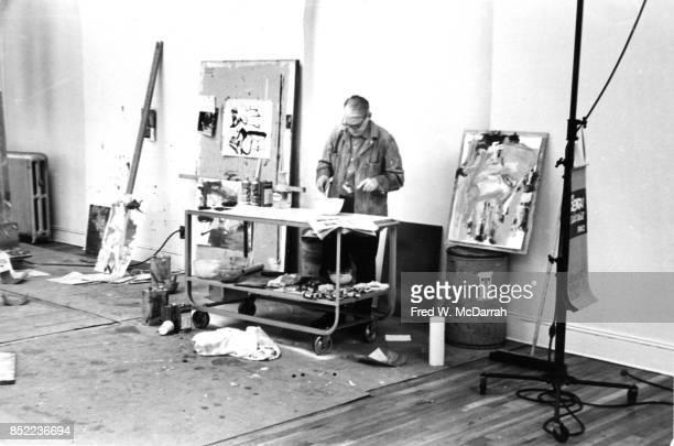 View of Dutchborn American artist Willem de Kooning as he mixes paint in his loft studio New York New York March 23 1962
