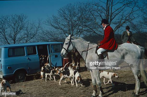 View of Dutchborn American horse trainer and riding instructor Harry de Leyer in equestrian clothing as he sits atop a horse while a large group of...