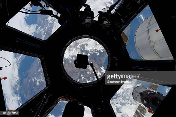 view of earth through the cupola on the international space station. - international space station fotografías e imágenes de stock