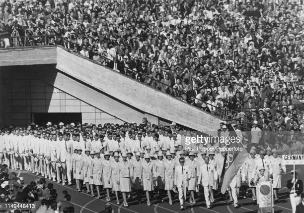 View of East German diver Ingrid EngelKramer holding the national flag as she leads the United Team of Germany Olympic team on to the track during...