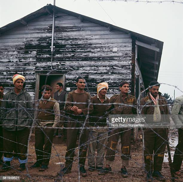 View of Egyptian prisoners of war standing behind a barbed wire fence being held captive at the Atlit detainee camp near Haifa Israel in December...
