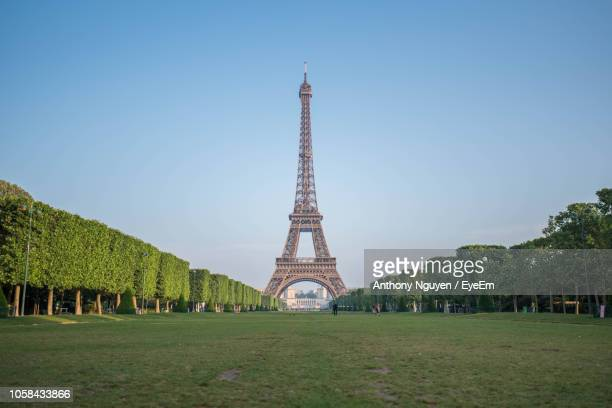 view of eiffel tower against clear blue sky - eiffel tower paris stock pictures, royalty-free photos & images