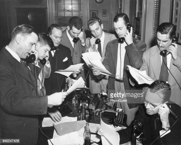 View of eight White House correspondents crowded around a table all on telephones Washington DC January 31 1950 They were reporting news of President...