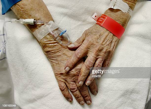 view of elderly womans hands with ivs and hospital bracelets - iv drip womans hand stock pictures, royalty-free photos & images