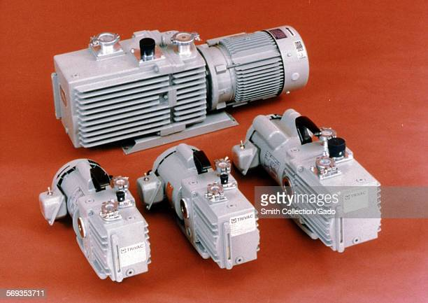 View of electric motors, with gearboxes attached, in four different sizes seen against a red background, 1966.