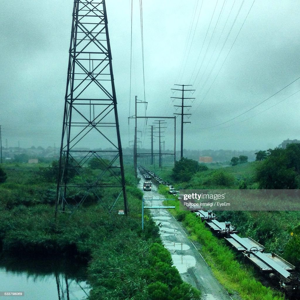View Of Electricity Pylons And Abandoned Train Chassis During Monsoon : Foto stock