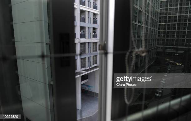 A view of employee dormitory is seen through a window equipped with protective net in Foxconn Technology Group's industrial complex in Longhua...