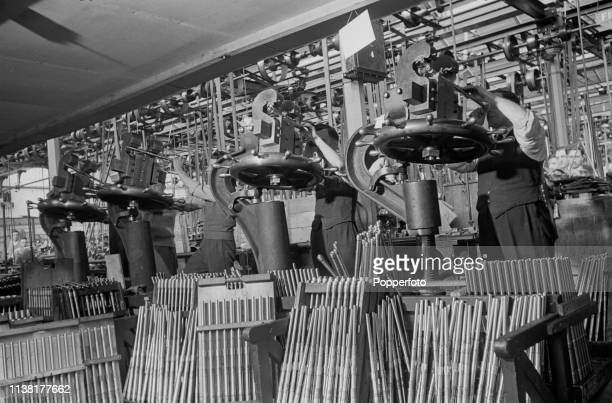 View of employees operating equipment to test and straighten the barrels of Bren light machine guns at the Royal Small Arms Factory in Enfield north...