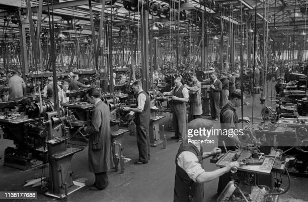 View of employees operating modern lathes in a large workshop to manufacture Bren light machine guns at the Royal Small Arms Factory in Enfield north...