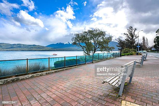 View Of Empty Bench By Calm Lake Against Cloudy Sky