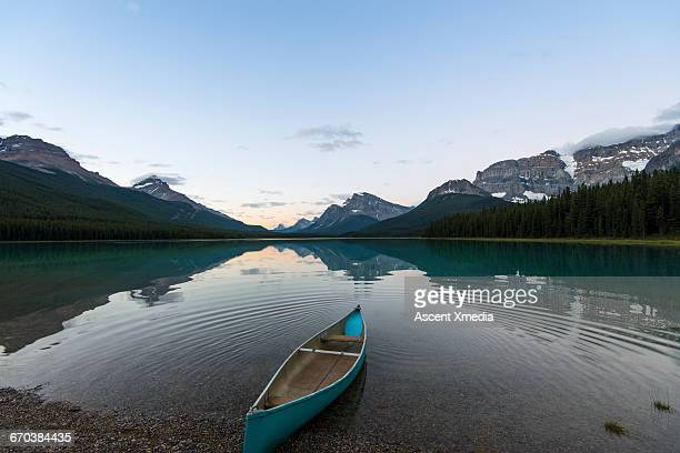 View of empty canoe on shore of mountain lake