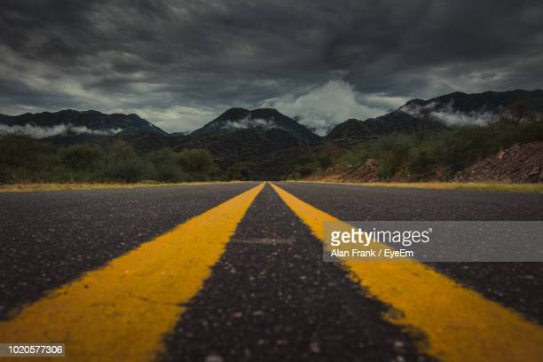 view of empty road against mountains - double yellow line stock photos and pictures