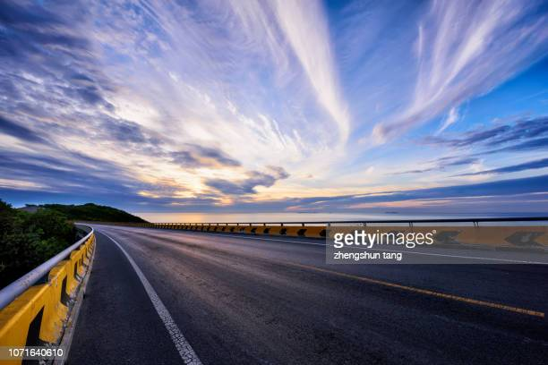 view of empty road by sea in the sunset - 海岸線 ストックフォトと画像