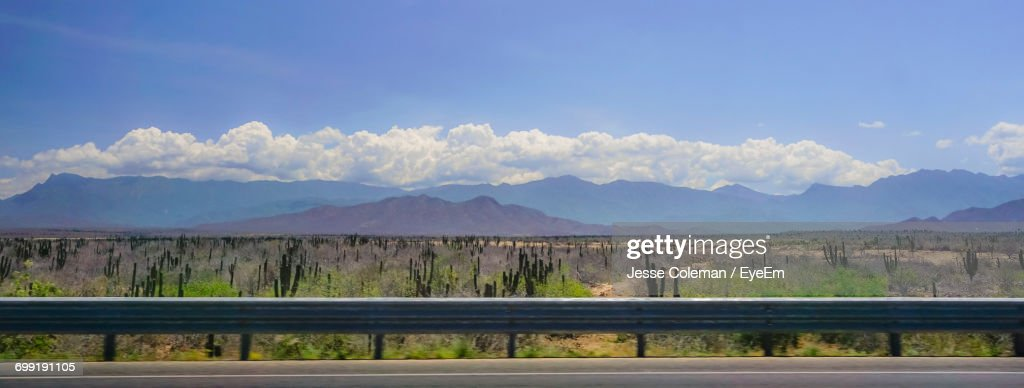 View Of Empty Road In Front Of Mountains Against Blue Sky : Stock Photo