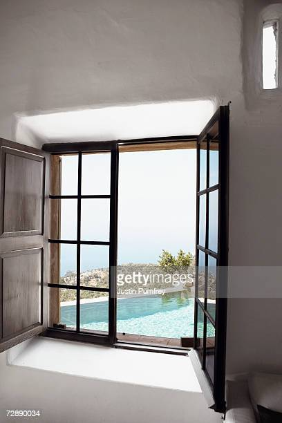 View of empty swimming pool through open window