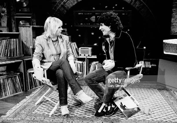 View of English Rock and Pop musician Christine McVie and American VJ Mark Goodman as they sit in director's chairs during an interview at MTV...