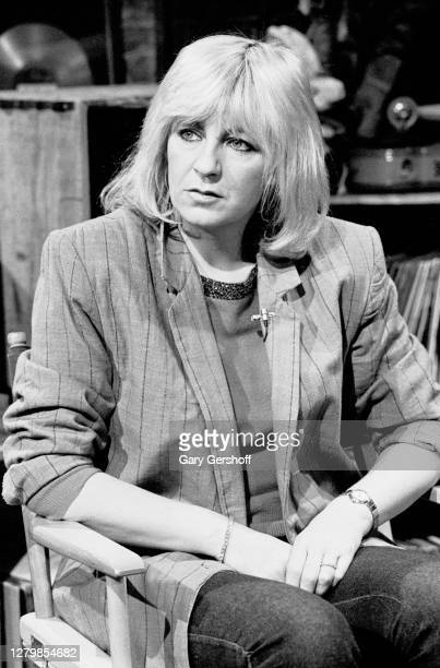 View of English Rock and Pop musician Christine McVie as she sits in a director's chair during an interview at MTV Studios, New York, New York, March...