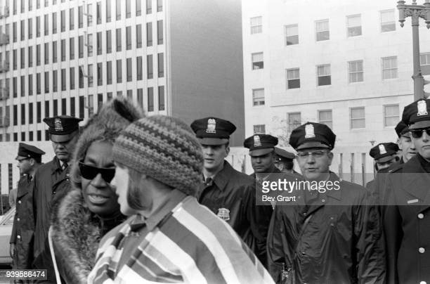 View of f activists Flo Kennedy and Cathy Barrett as watched by a large number of police officers they participate in the Jennette Rankin Brigade's...