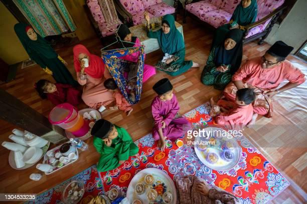 view of family in malaysia celebrating aidil fitri. - shaifulzamri stock-fotos und bilder