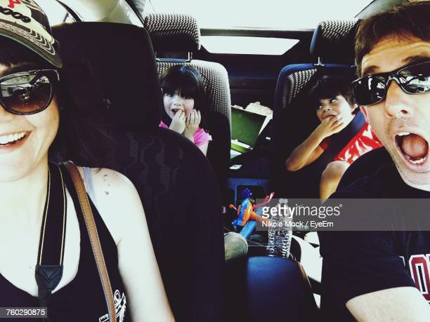view of family sitting in car - family inside car stock photos and pictures