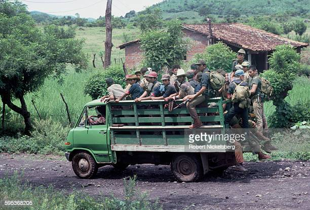 View of Farabundo Marti National Liberation Front guerrillas in the back of a truck as they travel on a dirt road in a rural farm district, central...
