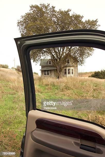 View of farmhouse through open car door