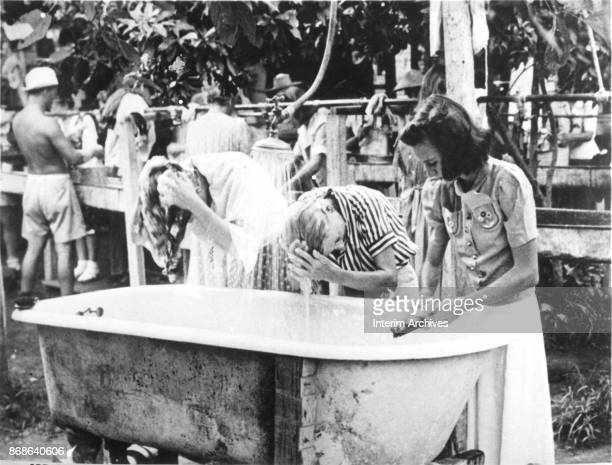 View of female prisoners as they wash their hair in a bathtub in a courtyard on the Santo Tomas University campus which had been used as a civilian...