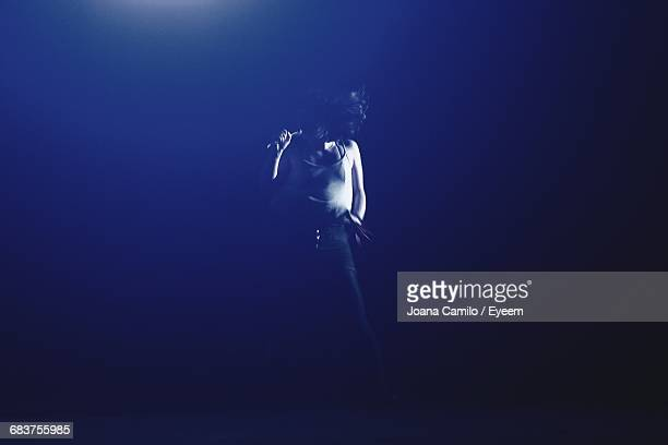view of female singer performing on stage in the dark - chanteur photos et images de collection