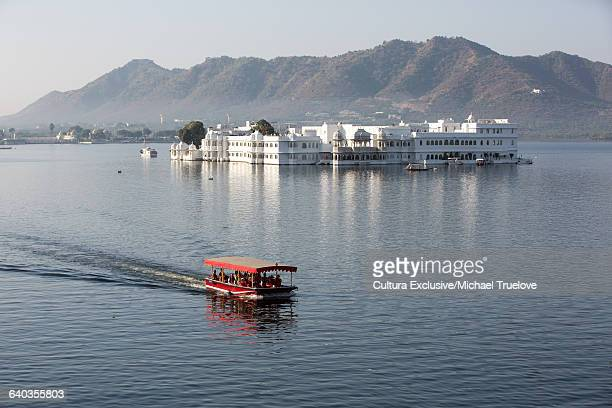 View of ferry and Lake Palace hotel, Udaipur, Rajasthan, India