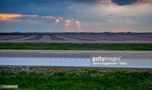 view of fields on flat land behind road - gerold guggenbuehl stock-fotos und bilder
