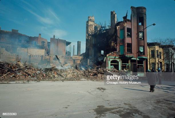 View of firemen looking at the smoldering ruins of a destroyed building in the west side neighborhood of Lawndale after the rioting which occured...