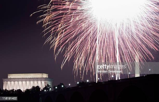A view of fireworks above the Lincoln Memorial Washington Memorial and Memorial Bridge on the National Mall in Washington DC from along the shore of...