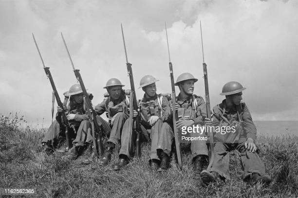 View of five British Army soldiers sitting with bayonets drawn on their LeeEnfield SMLE rifles as they guard the White Cliffs of Dover between the...