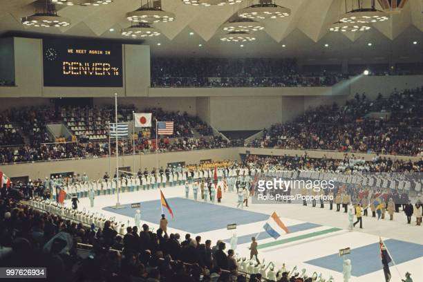 View of flag bearers and athletes from competing countries standing together and participating in the closing ceremony of the 1972 Winter Olympics...