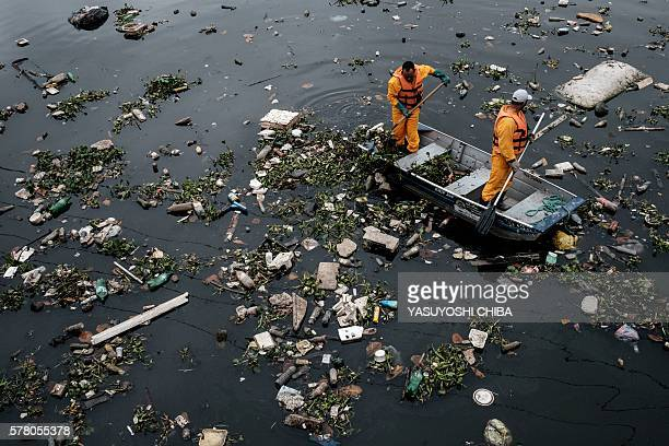 TOPSHOT View of floating debris carried by the tide and caught by the 'ecobarrier' before entering Guanabara Bay at the mouth of Meriti river in...