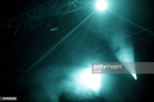 A view of foggy stage lights emerging from the dark