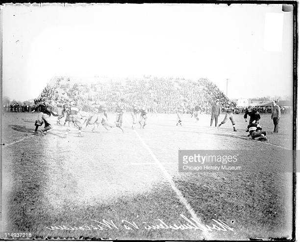 View of football players running and grappling on an athletic field in Evanston Illinois during a football game between the Northwestern University...