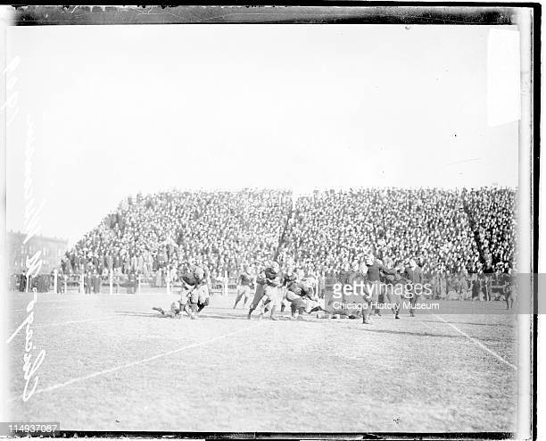 View of football players running and grappling on the field during a football game between the Northwestern University and Wisconsin football teams,...