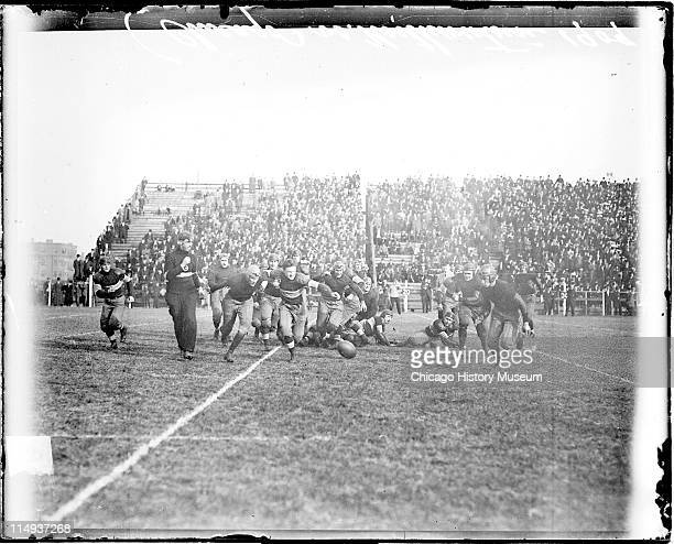 View of football players running towards a football lying on the ground during a football game between the University of Chicago and Northwestern...