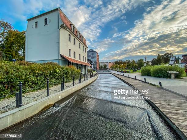 view of footpath by buildings against sky - bydgoszcz stock pictures, royalty-free photos & images
