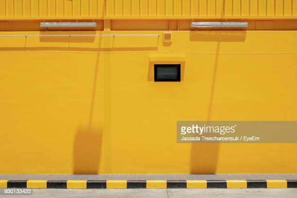 view of footpath with yellow building - yellow stock pictures, royalty-free photos & images