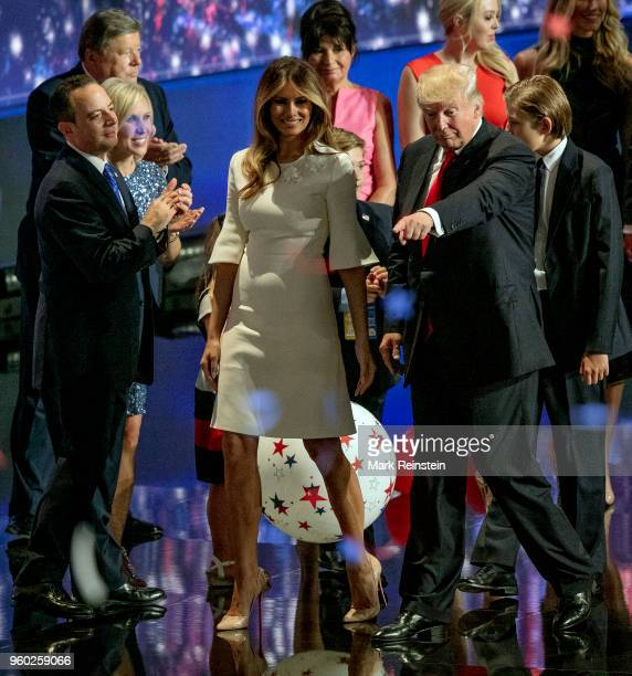 View of former model Melania Trump and real estate developer presidential candidate Donald Trump hold hands as the latter points from the stage at...
